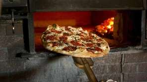 Pizza is baked in a coal-fueled oven at