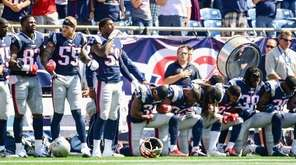 Members of the New England Patriots kneel on