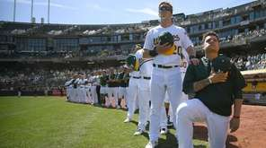Bruce Maxwell of the Oakland Athletics kneels in