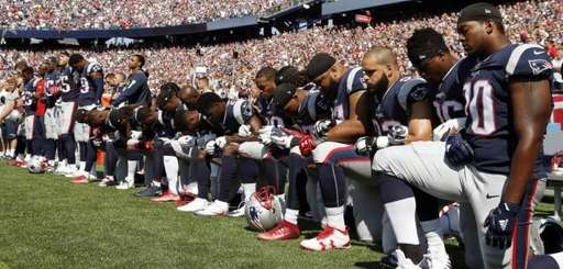 Several New England Patriots players kneel during the