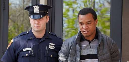 A police officer escorts Christopher James from the