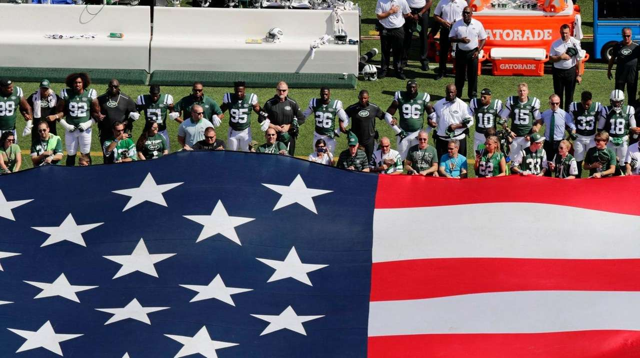 The New York Jets lock arms during the