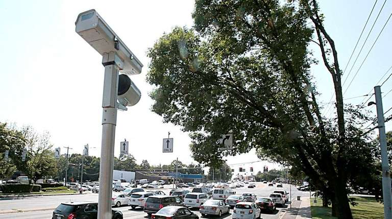 A red light camera on the corner of