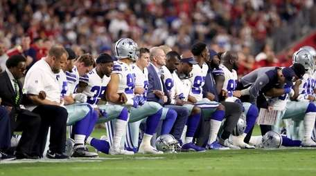 Members of the Dallas Cowboys link arms and