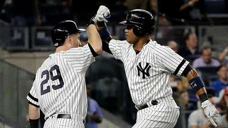 Yankees' Starlin Castro, right, and Todd Frazier high-five
