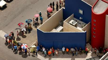 A line extends around a Banco Popular branch