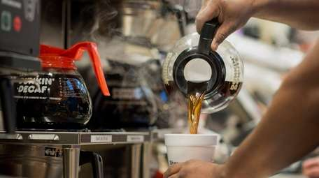 An employee fills a cup with coffee at