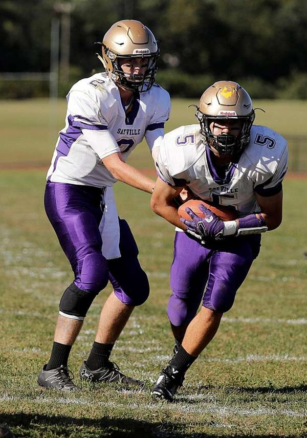 Sayville quarterback Jacob Cheshire hands off to running back