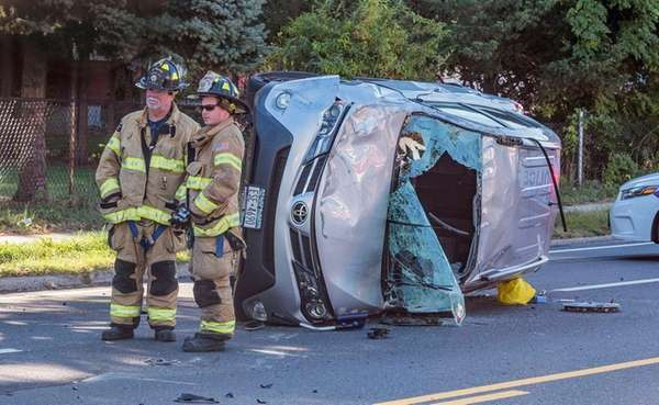 Firefighters stand near an overturned vehicle, one of