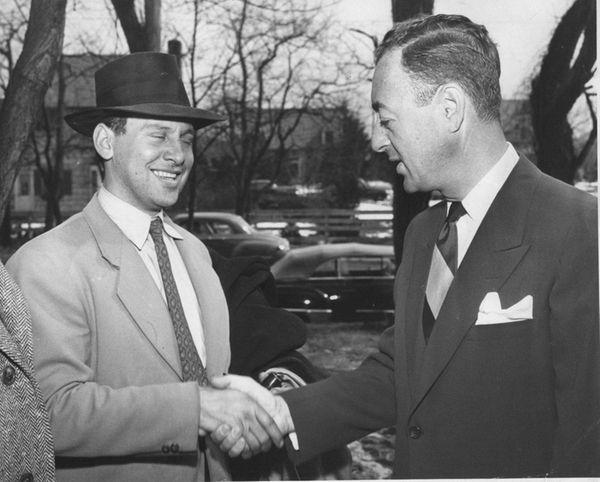 Builder William Levitt, right, congratulates Mortimer Weiss of