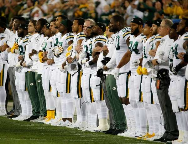 Green Bay Packers link arms during the national