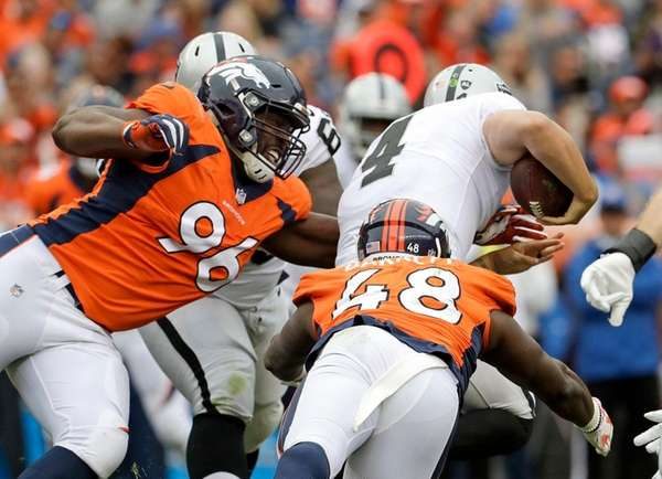 Raiders quarterback Derek Carr is tackled by Broncos