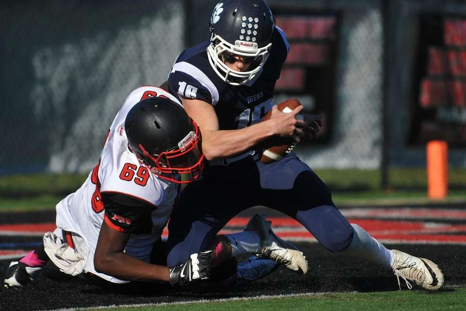 Jamar King of Patchogue-Medford, left, sacks Northport quarterback