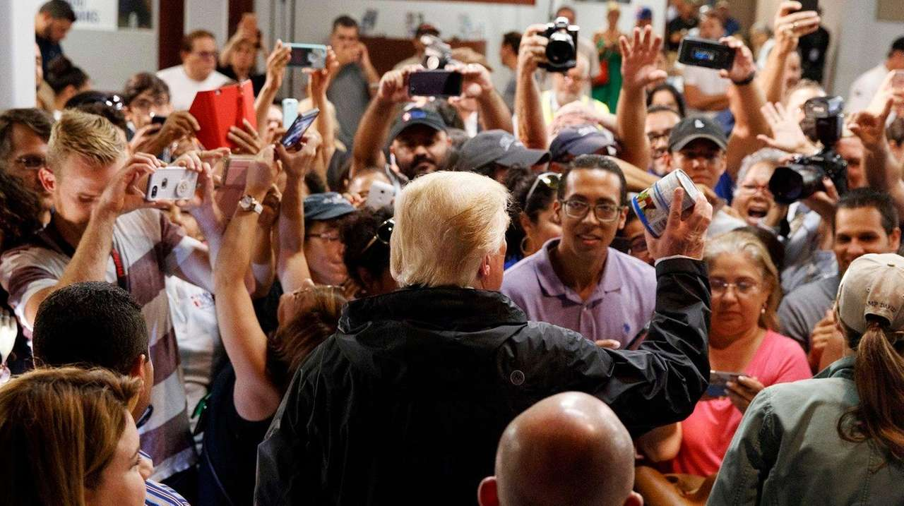 President Donald Trump hands out canned goods and