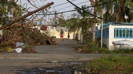 A man and child walk down street strewn