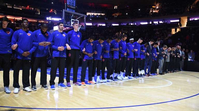 Knicks players and coaches linkarms during the national