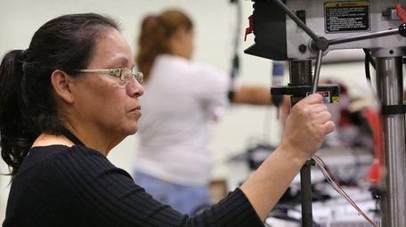 Assembly operatorSonia Ramirez assembles LED lighting fixtures at