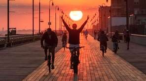 A cyclist wheels down the Long Beach Boardwalk