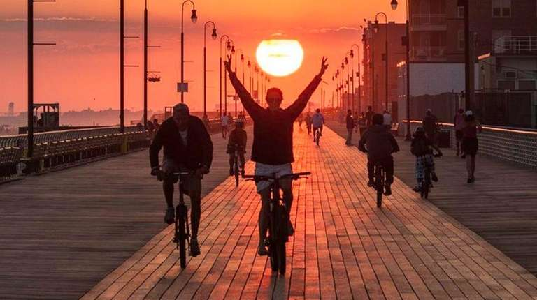 A cyclist wheels down the Long Beach Boardwalk
