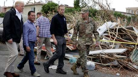 President Donald Trump walks with FEMA administrator Brock