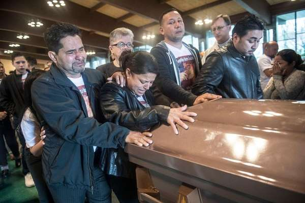 Carlos Lopez and Lourde Banegas mourn by the