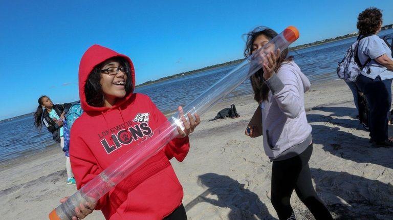Seventh-grader Griselda Portillo, left, holds a shoreline sediment