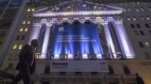 A pedestrian walks past the NYSE on Wall