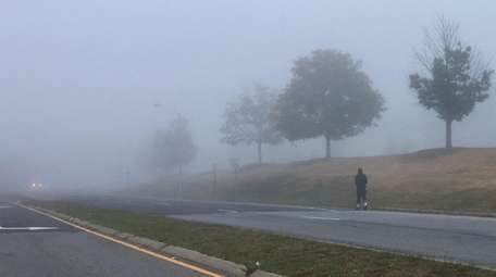 A man walks through a blanket of fog