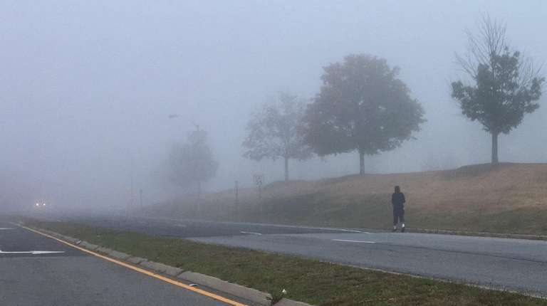 A man walks through a blanket of fog