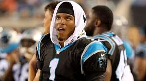 Cam Newton of the Panthers watches the scoreboard