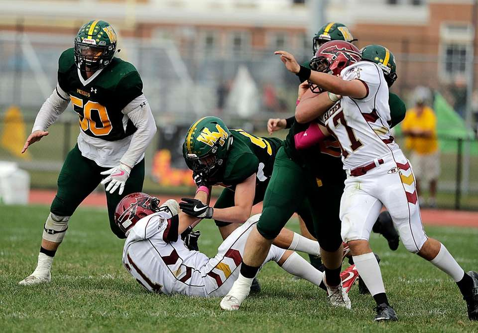 Ward Melville's offensive lineman Timothy Kutchma (50) seals