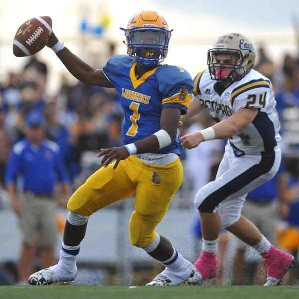 Christian Fredericks #1, Lawrence quarterback, left, scrambles to