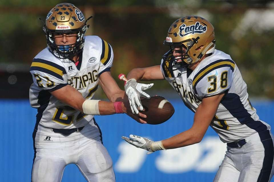Jason Seiter #23, Bethpage quarterback, left, hands off