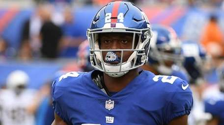 Giants cornerback Eli Apple looks on from the