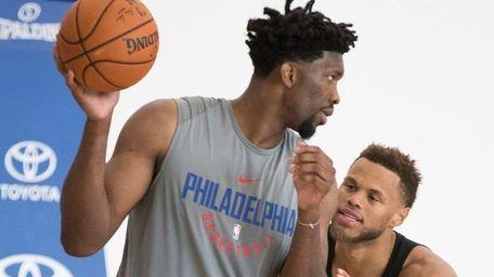 Philadelphia 76ers' Joel Embiid, left, does a post-up