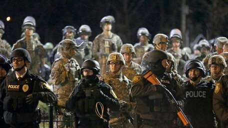 Police and Missouri National Guardsmen stand guard as