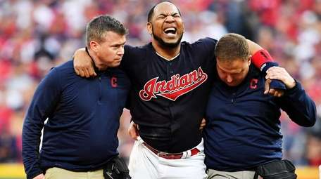 Edwin Encarnacion of the Indians receives medical attention after an