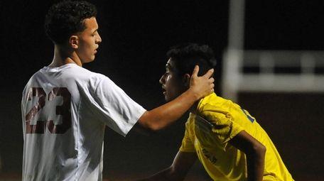 Josue Fuentesof Glen Cove, left, gives Mauricio Puerto-Quintanilla