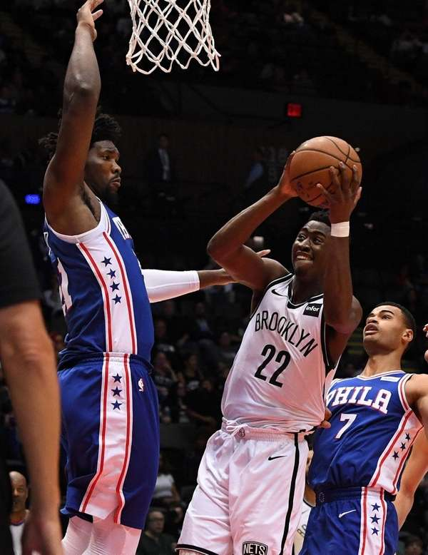 Nets guard Caris LeVert is defended by76ers center