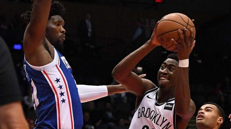 Nets guard Caris LeVert is defended by 76ers center