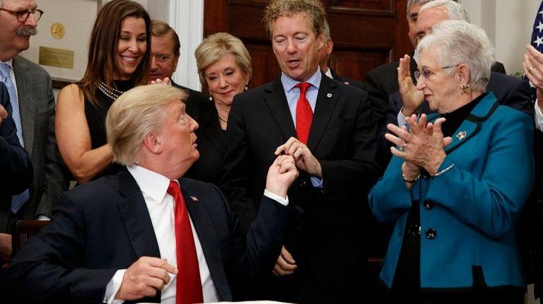 President Donald Trump hands a pen that he