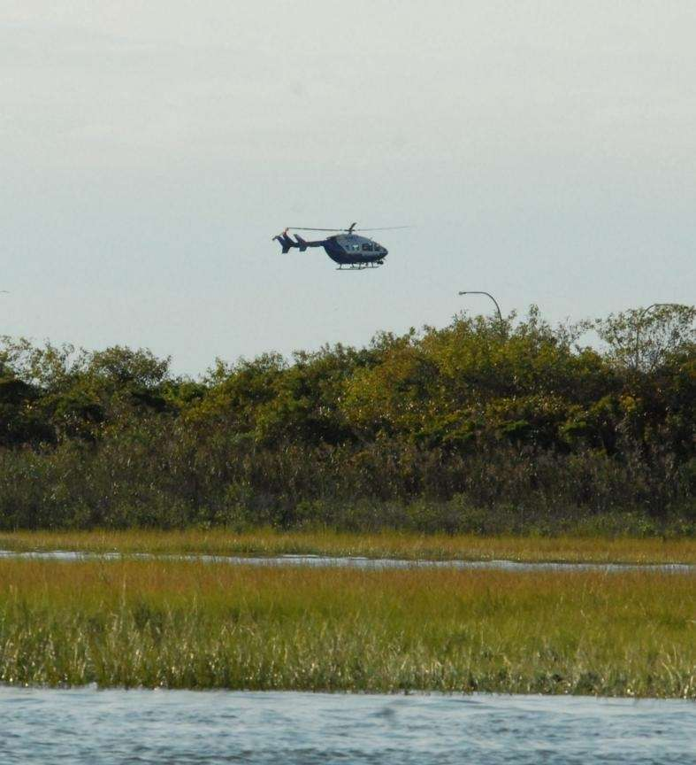 A police helicopter flies over the marshes near