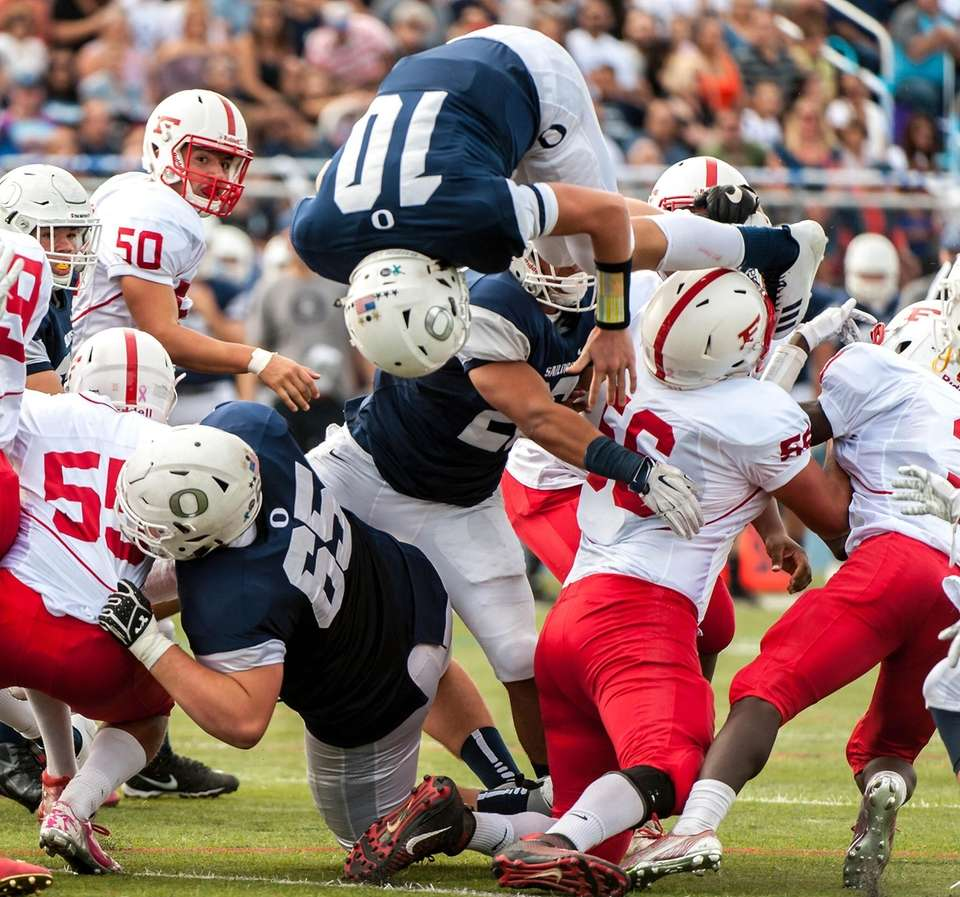 Oceanside QB Tommy Heuer dives over the players