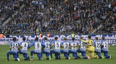 Hertha Berlin's players kneel down before the German