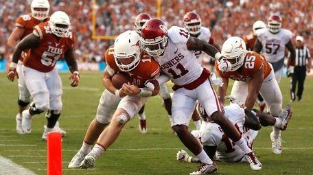 Texas quarterback Sam Ehlinger, center left, collides with