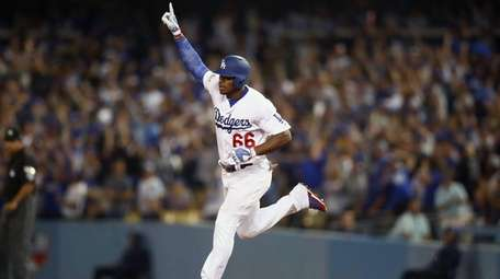 Dodgers outfielder Yasiel Puig celebrates after hitting a