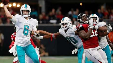 Dolphins quarterback Jay Cutler throws the ball under
