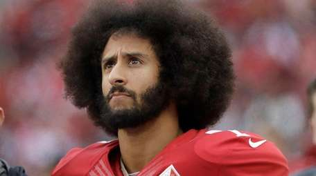 49ers quarterback Colin Kaepernick stands in the bench