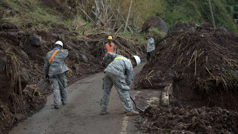 Soldiers shovel debris on a road near Adjuntas,