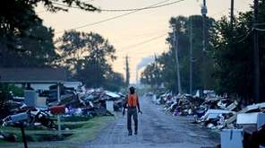 A man walks past debris from homes on